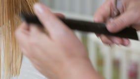 做理发的美发师特写镜头对有剪刀的妇女在美发店 理发过程 理发被漂白的头发 影视素材