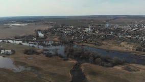 Bird's eye view of the overstromende River near the villages De rivier stroomde in de buurt van de dorpen De overstroming van de stock videobeelden