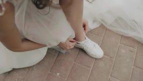 Sposa allegra che lega i suoi laccetti sulle sue scarpe da tennis sposa fresca di divertimento bello vestito bianco come la neve stock footage