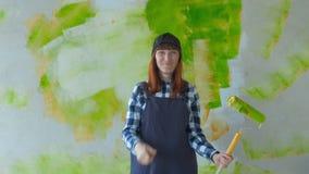 一个小女孩修理 那个拿着滚轮的女孩给墙涂漆 那个女孩修理,微笑 绘制 股票录像