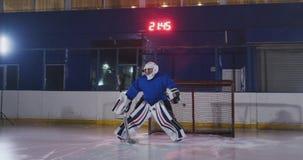 Un giocatore di hockey professionista attacca il cancello e colpisce, ma il portiere batte il burattino Un goal nell'hockey Obiet video d archivio