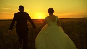 Een paar in liefde handen vasthouden gaat naar zonsondergang Vrolijke man en vrouw rennen op zonsondergang Een paar verliefd op e stock video