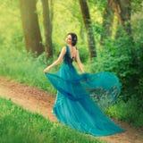 Dziewczyna w wieczór, luksusowym, wyborcy koloru suknia z otwartym z powrotem, z latającym pociągiem, iść wzdłuż ścieżki _ zdjęcie stock