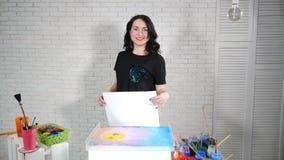 Mooie vrouwelijke kunstenaar met een blanco papier in handen Glazen potten met verf en borstels overal Het portret van glimlachen stock video