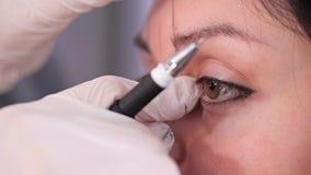 Nahe Augen, Mädchenaugen Der Spezialist zeichnet die richtige Form der Augenbrauen mit einem Faden Schönheitsklinik 4 K Langsam stock footage