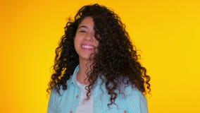 Het portret van een jong mooi meisje corrigeert haar krullen op gele achtergrond Trendy schattige vrouw glimlacht naar camera Stu stock video