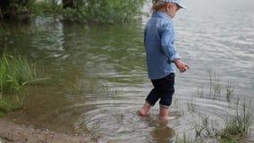 小男孩沿河散步 孩子在湖边跑 慢动作 在水边玩耍的快乐婴儿 影视素材