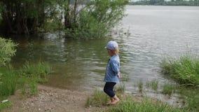 小男孩沿河散步 孩子在湖边跑 慢动作 在水边玩耍的快乐婴儿 股票录像