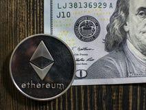 E r Vraies pièces de monnaie de bitcoin sur le billet de banque de cent