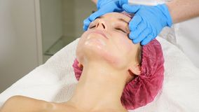 Beauticians w niebieskich rękawiczkach nakłada śmietanę na twarz młodych kobiet Koncepcja naprawy i odmłodzenia twarzy Zamykanie  zdjęcie wideo