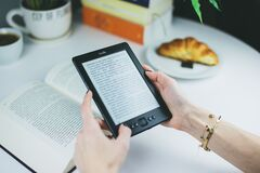 E-reader and book Stock Image