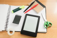 Elearning still life education concept. E-reader with nothing on screen with various office items like scissors, scotch tape, note blocks, marker, an empty royalty free stock image