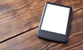 E-reader/tablet on wood table. E-reader on old wood table. Tablet on wood background Stock Images