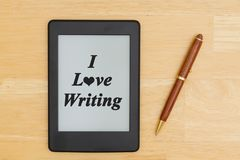 An e-reader on a wood desk with a pen with text I love writing stock images