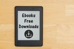 An e-reader on a wood desk with text ebooks Free Downloads. An e-reader on a desk with text Ebooks Free Downloads and a download icon royalty free stock photography