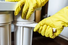 E Repairman zmienia wodne filtrowe ?adownicy w kuchni obraz stock