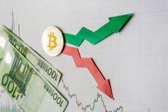 E Rode en groene pijlen met gouden Bitcoin-ladder op grijs document royalty-vrije stock fotografie