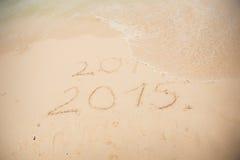 2014 e 2015 scrivono sulla sabbia bianca Immagini Stock