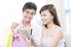 E-shoppers. Excited couple considering new ways of doing shopping together Stock Image