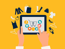 E-shopping concept. Hands touching a tablet with shopping icons. Stock Photos