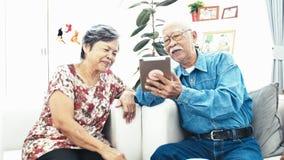 E-shopping senior asiatico delle coppie con la compressa digitale video d archivio