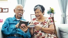 E-shopping senior asiatico delle coppie con la compressa digitale stock footage