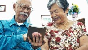 E-shopping senior asiatico delle coppie con la compressa digitale archivi video