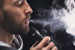 E-sigaretta vaping del giovane con fumo sul nero fotografia stock libera da diritti