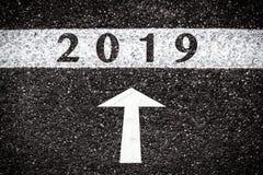 2019 e sinal da seta na textura do asfalto fotografia de stock