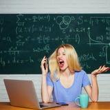 E Situaci?n del conflicto Freelancer de la mujer con buen humor usando el ordenador port?til foto de archivo