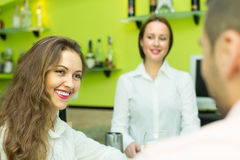 Żeński barista i dwa klienta w kawiarni Zdjęcia Royalty Free