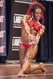 Żeński bodybuilder w triceps, klatki piersiowej czerwieni i pozy bikini i Zdjęcia Stock