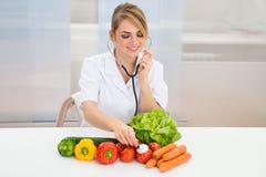 Żeński dietician egzamininuje warzywa Fotografia Royalty Free