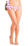 Żeńskie nogi z storczykowym kwiatem na bielu Obraz Stock