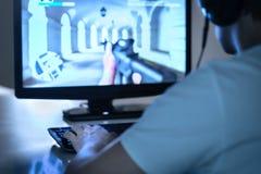 E-sportar och spelabegrepp Gamer som spelar FPS-videospelet med datoren och bär hörlurar Yrkesmässig videogamespelare royaltyfria bilder