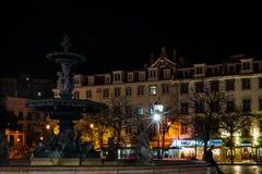 E Springbrunn i i stadens centrum Lissabon på natten arkivbilder