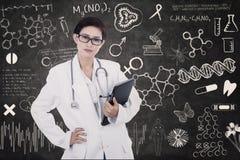 E-tabuleta fêmea segura da posse do doutor no quadro-negro escrito Fotos de Stock