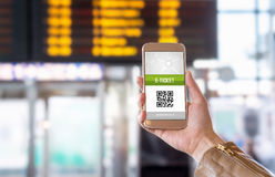 E-ticket on smartphone screen. With timetable in the blurred background. Buying online ticket from internet. Universal public transportation terminal. Bus Stock Images