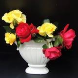 E um ramalhete de rosas vermelhas em um vaso branco em um fundo preto Foto de Stock Royalty Free