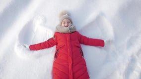 E Uma menina bonita em um revestimento encontra-se na neve, espalhando seus braços vídeos de arquivo