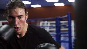 E Un boxeur fâché met un poinçon dans un sac de boxe dans les gants noirs banque de vidéos