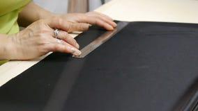 E Una modista que corta un negro de alta calidad de la tela, antes de que usted lo cosa y lo haga metrajes