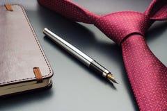 E Una pluma con un cuaderno miente en un lazo Imagen de archivo libre de regalías