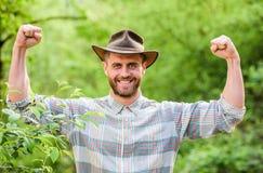 E uomo muscolare del ranch nelle piante di cura del cappello da cowboy Agricoltura ed agricoltura r Azienda agricola di Eco immagini stock