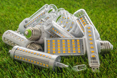 E27, USB and R7s ecological and economical LED bulbs. Ecological and economical LED bulbs of various types on the green grass Royalty Free Stock Photos
