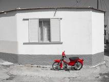 E Velomotor vermelho ao lado da casa branca tradicional preto e branco da vila imagens de stock