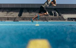 Sprinter taking off for a run from the start line. E view of an athlete starting his sprint on an all-weather running track. Runner practicing his sprint on a Royalty Free Stock Photography