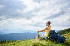 Woman hiker hiking on grassy hill, wearing backpack, using trekking sticks in the mountains. E view of attractive woman hiker resting on grassy hill with royalty free stock photography