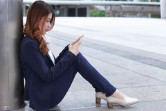 Side view of beauty young Asian business woman in formal clothes sitting on floor and looking on mobile smart phone at urban with Stock Photo