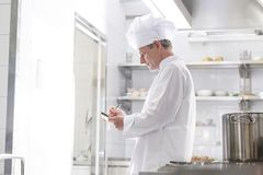 Side view of chef writing on notepad while standing in kitchen at restaurant. E view of chef writing on notepad while standing in kitchen at restaurant royalty free stock photography